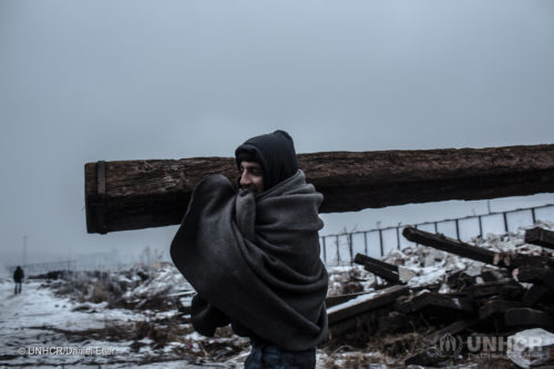 Men carry a railway sleeper to a fire place behind the train station in Belgrade. ; In the winter of 2016/2017, thousands of refugees were stuck in the Balkans. Many squatted in abandoned buildings in central Belgrade, with temperatures reaching minus 13 degrees centigrade at night. UNHCR was working to transfer people sleeping in rough conditions to government shelters.